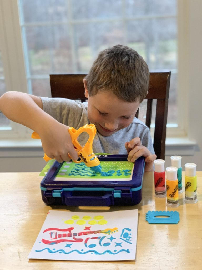 child using the play-doh dohvinci on the go set.