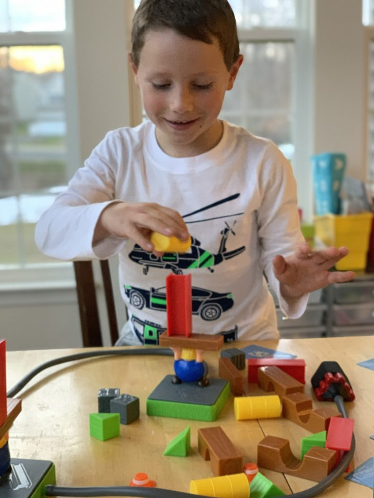 a boy building his set while playing the Build or Boom Game
