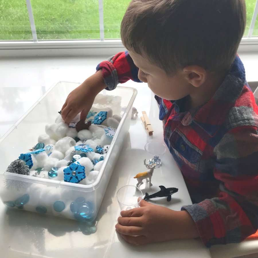 A child engaging with the winter activity for preschoolers. A great boredom buster for indoor play. Winter Sensory Bin.