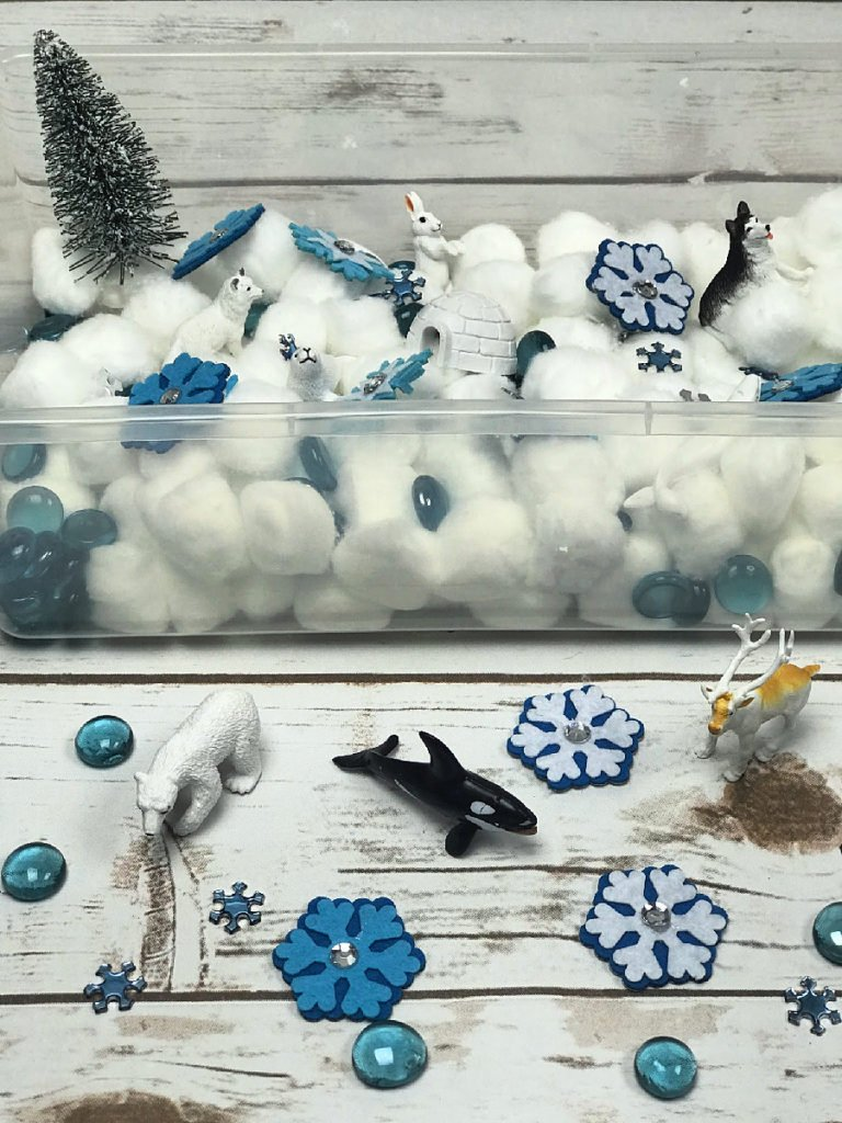 A plastic bin with cotton balls for snow and plastic arctic animals, blue glass gems, and small snowflakes.