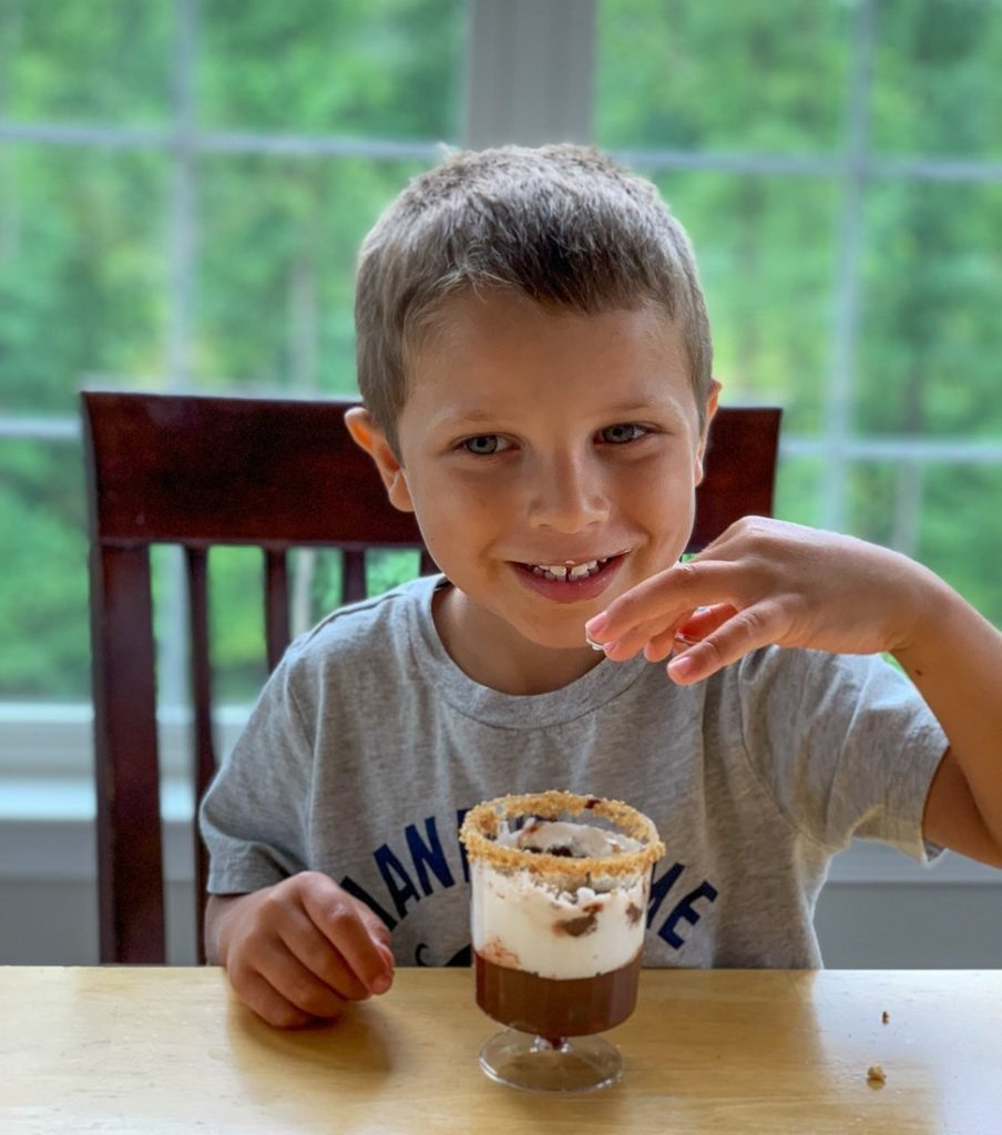 A little boy tasting the s'mores recipe with a big smile as he takes a bite of the s'mores parfait.
