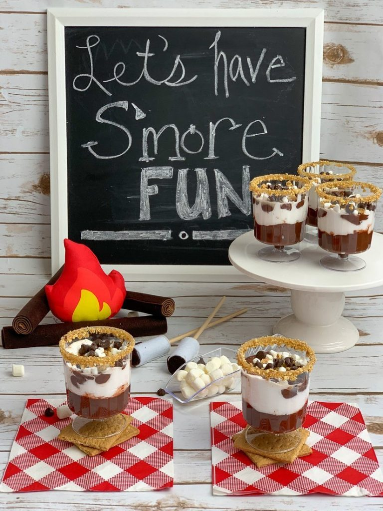 A s'mores bar display with five parfait cups with the s'mores recipe and a chalkboard sign that reads Let's Have S'more Fun