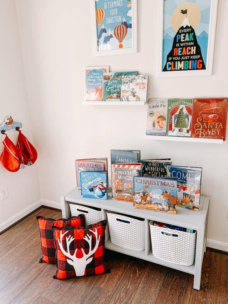 two wall shelves displaying Christmas books and a small wooden bench displaying Christmas books.